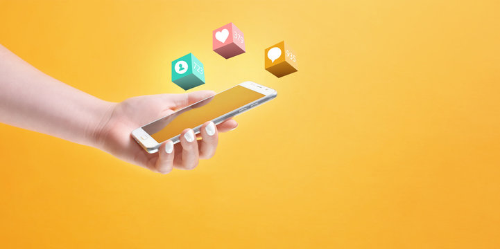 Girl's hand holding smartphone in hand, surrounded with social media notification icons on yellow background