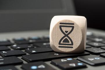 Würfel auf Tastatur mit Sanduhr Zeitmanagement