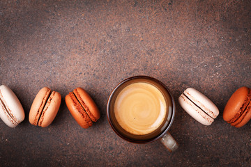 Cup of fresh coffee and cake macaron or macaroon on brown table top view.