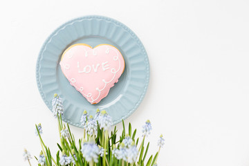 Heart shape cookie with love sign on white textured background