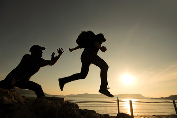 Asia couple hiking help each other silhouette in mountains with sunlight.Silhouette man lifts his hand on a rocky seashore.