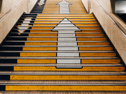 Big arrows direction symbol on concret stair in subway in Japan. there is seperate the walk way clearly. Line up and down.