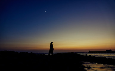 silhouette of a man on the beach at sunset