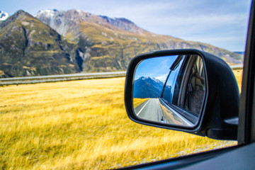 Roadtrip/car traveling concept. View of back car mirror with mountain and road scenery. Aoraki/Mount Cook National Park, South Island of New Zealand.