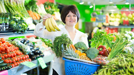 Mature woman buying fresh fruits and vegetables