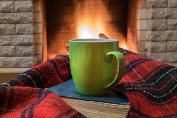 Cozy scene before fireplace with big green mug of tea, a book, and wool scarf.