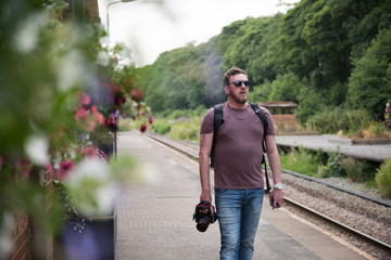london, england, A male photographer wearing sunglasses walking along a vintage traditional train station platform in the British countryside. Amateur photographer.