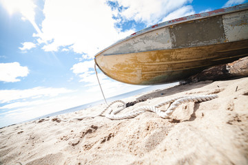 Old metal fishing boat on the coast of the sea on a sunny day