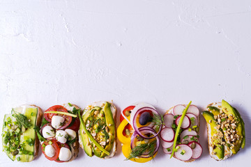 Sandwiches or tapas with bread , cream cheese, vegetable and tasty toppings. Healthy food for lunch or breakfast. Copy space for your text. Flat lay.