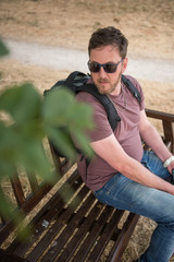 london, england, 01/01/2019 A man sitting on a beautiful dark brown rustic weathered wooden hand made bench, photographed from above. Bench in in a dry summer park setting.