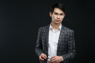 Young аsian businessman isolated on a dark background.