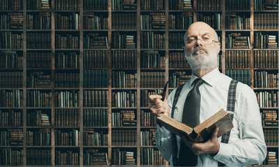 Academic professor in the library holding a book
