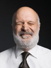 Cheerful senior businessman portrait on black background