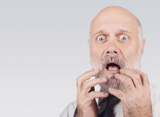 Terrified senior man gasping and looking at camera