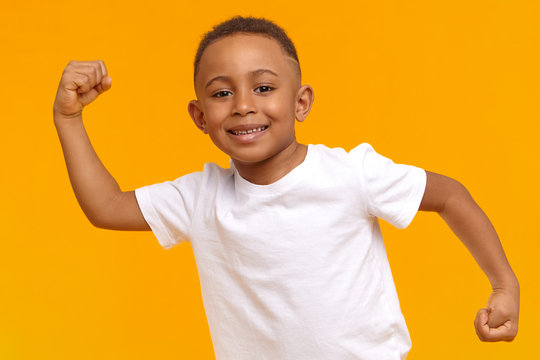 Body language. Picture of handsome Afro American 8 year old kid dressed in casual wear posing isolated at yellow wall, raising clenched fists and tensing bicep, demonstrating his strong arms