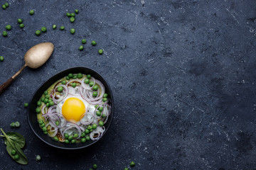 Green pea soup with fried egg and red onion on dark background, top view.