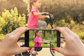 Woman use mobile phone and blurred image of a boy ride the bicycle in the park