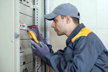 Electrician using a tester on an industrial panel in a factory
