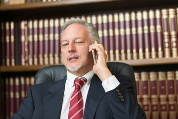 Business man lawyer using his cell phone to make a call from his studio office