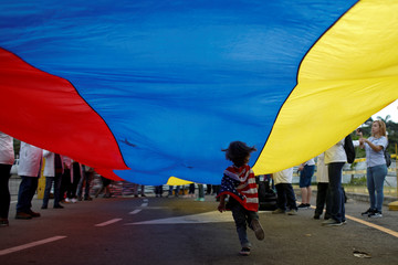 A child wearing a U.S. flag runs under a Venezuelan flag during a gathering of Venezuelan doctors at the entrance of a warehouse where humanitarian aid for Venezuela is being stored in Cucuta