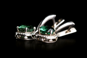 Jewelry silver earrings with green stone on a black background. Isolation