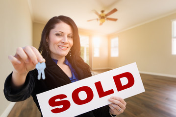 Hispanic Woman With House Keys and Sold Real Estate Sign In Empty Room of House