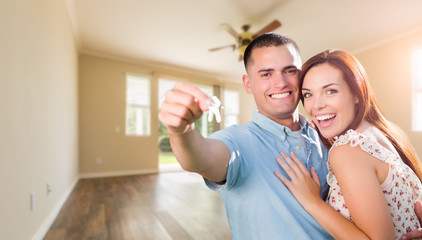 Young Military Couple with House Keys In Empty Room of New Home