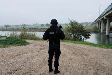 A Mexican federal police officer stands on the bank of Rio Bravo as cars belonging to U.S. security forces can be see at the other side of the river, in Piedras Negras