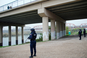Mexican federal police officers stand on the bank of the Rio Bravo near a bridge connecting Eagle Pass, Texas, with Piedras Negras, in Piedras Negras