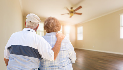 Senior Couple Looking Into Empty Room of House