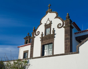 Detail of front facade of white Marian sanctuary of Nossa Senhora da Paz, Our Lady Of Peace Chapel, beautiful small chapel on a high hill above the village of Vila Franca do Campo in Sao Miguel island