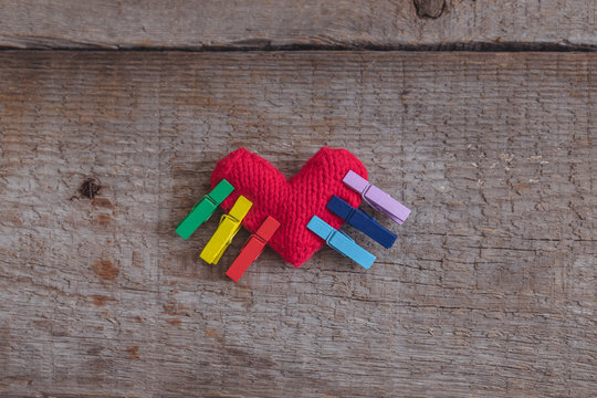 LGBT rainbow knitted heart symbol of love on wooden background, concept