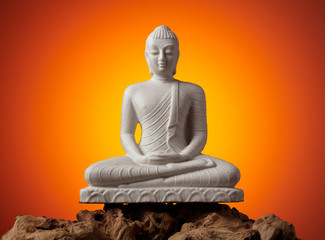 The white buddha figure stands on the texture wood.