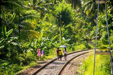 The natives family walking on railway tracks in Sri Lanka.