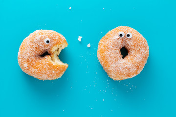 Funny doughnuts with eyes, cartoon like characters, on blue background.