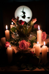 Enchanted tea surrounded by burning candles, with flowers in a cup. Silhouette of a witch on the background of a bright moon.