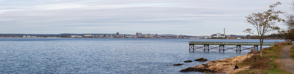 Panoramic view of a wooden quay on the Atlantic Ocean Coast during a cloudy morning. Taken in Lighthouse Point Park, New Haven, Connecticut, United States.