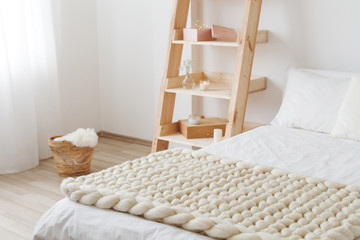 Light beige knitted woolen merino chunky blanket on bed with white linen. Thick yarn. Stylish cozy...