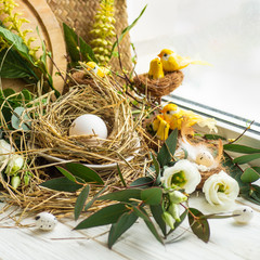 Happy Easter background. Easter egg in a nest with floral decoration near the window. Quail eggs. Happy Easter concept