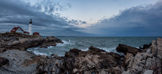 Beautiful panoramic view of Portland Head Lighthouse on the Atlantic Ocean Coast during cloudy sunset. Taken in Fort Williams Park, Portland, Maine, United States.