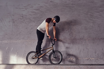 Full body portrait of a young man in protective helmet with his bike standing in a skatepark indoors