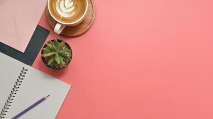 Flat lay, top view office table desk. Workspace with blank clip board, keyboard, office supplies, pencil, green leaf, and coffee cup on pink background