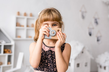 Small girl looking out of wooden photocamera