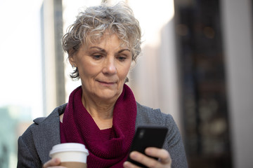 Mature woman in city walking texting on cell phone
