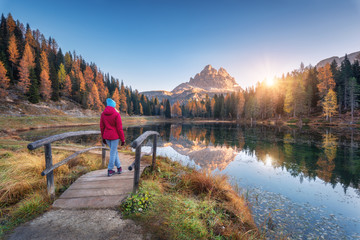 Young wooman on the small wooden bridge against lake, autumn forest, mountain peak, blue sky with sunlight at sunrise. Landscape with girl, reflection in water, green grass, rocks in Dolomites, Italy