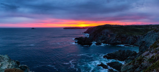 Striking panoramic seascape view on a rocky Atlantic Ocean Coast during a colorful sunrise. Taken at Crow Head, North Twillingate Island, Newfoundland and Labrador, Canada.