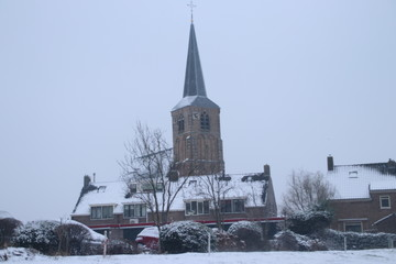 snow in the old part of the town Nieuwerkerk aan den IJssel around ring canal Zuidplaspolder and on willows in the Netherlands