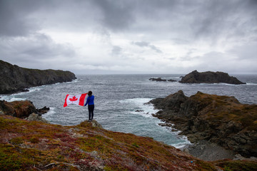 Fototapete - Adventurous woman holding a Canadian Flag on a Rocky Atlantic Ocean Coast during a cloudy day. Taken in Sleepy Cove, Crow Head, Twillingate, Newfoundland, Canada.