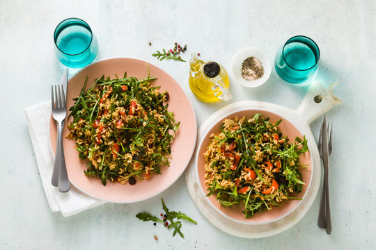 rice salad with baked bell peppers, arugula, olives and capers. Healthy vegan spring recipe for the whole family or party