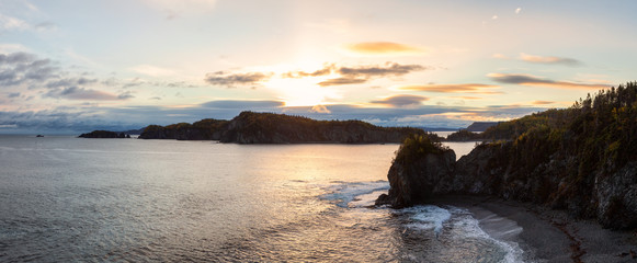 Striking panoramic landscape view of a rocky Atlantic Ocean Coast during a vibrant sunrise. Taken at Beachside, Newfoundland and Labrador, Canada.